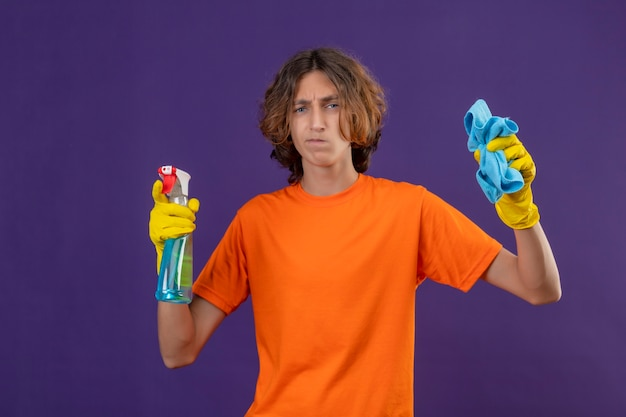 Young man in orange t-shirt wearing rubber gloves holding cleaning spray and rug looking at camera with skeptic expression on face standing over purple background