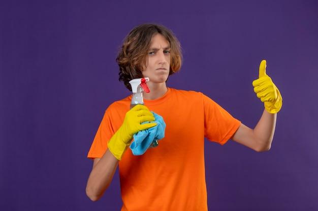 Giovane uomo in maglietta arancione che indossa guanti di gomma tenendo spray per la pulizia e rug guardando la fotocamera con un sorriso scettico sul viso che mostra i pollici in su in piedi su sfondo viola