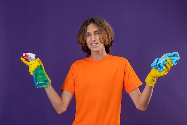 Giovane uomo in maglietta arancione che indossa guanti di gomma tenendo spray per la pulizia e rug guardando la telecamera con il sorriso sul viso pronto per pulire in piedi su sfondo viola