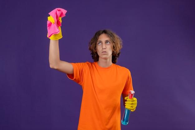 Giovane uomo in maglietta arancione che indossa guanti di gomma tenendo spray per la pulizia e tappeto cercando dispiaciuto pronto per pulire in piedi su sfondo viola