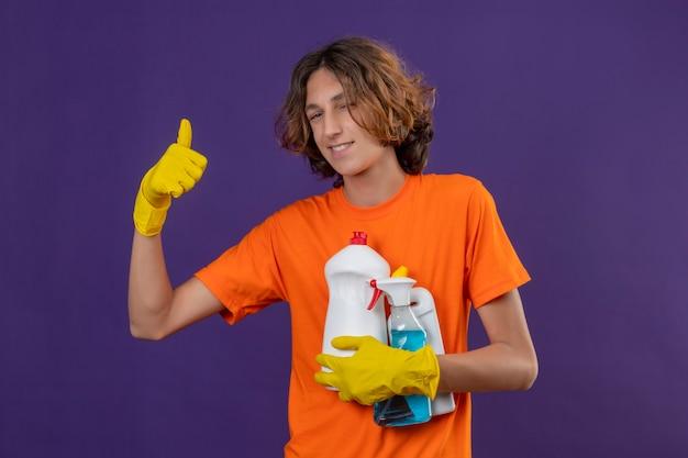 Giovane uomo in maglietta arancione che indossa guanti di gomma tenendo gli strumenti per la pulizia guardando la fotocamera con un sorriso fiducioso che mostra i pollici in su in piedi su sfondo viola