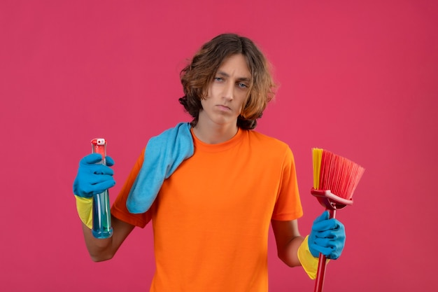 Young man in orange t-shirt wearing rubber gloves holding mop and cleaning spray looking at camera with sad expression on face standing over pink background