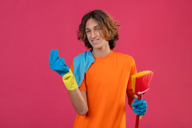 Giovane uomo in maglietta arancione che indossa guanti di gomma tenendo mop e rug guardando la fotocamera con un sorriso fiducioso sul viso facendo soldi gesto in piedi su sfondo rosa