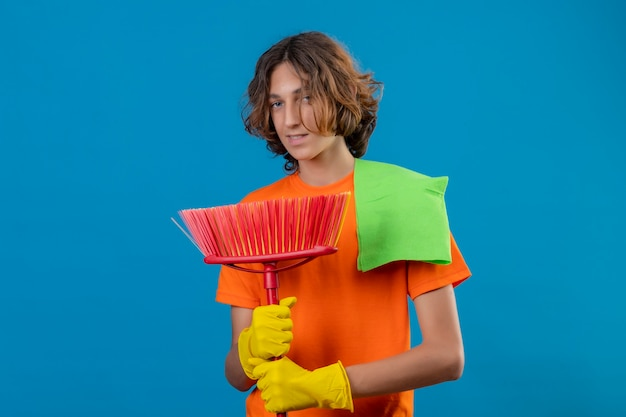 Young man in orange t-shirt wearing rubber gloves holding mop and rug looking at camera with confident smile on face standing over blue background