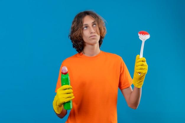 Giovane uomo in maglietta arancione che indossa guanti di gomma tenendo la spazzola per strofinare e la bottiglia con prodotti per la pulizia cercando il pensiero incerto avendo dubbi in piedi su sfondo blu