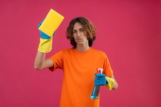Young man in orange t-shirt wearing rubber gloves holding sponge and cleaning spray looking at camera with sad expression on face standing over pink background