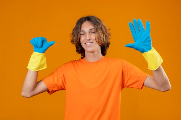 Young man in orange t-shirt wearing rubber gloves smiling with happy face showing and pointing up with fingers number six standing over yellow background