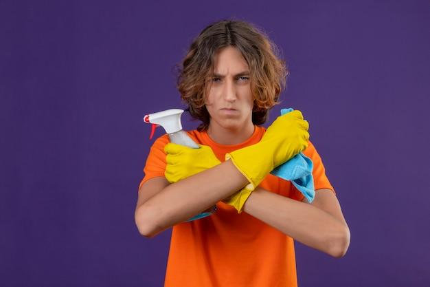 Giovane uomo in maglietta arancione che indossa guanti di gomma in piedi con le braccia incrociate tenendo spray per la pulizia e rug guardando la telecamera con espressione arrabbiata in piedi su sfondo viola