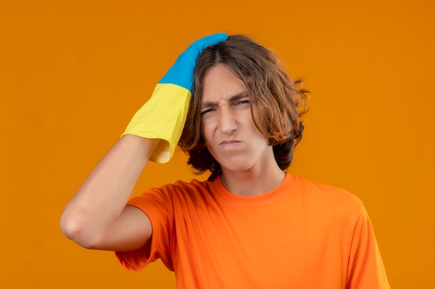 Giovane uomo in maglietta arancione che indossa guanti di gomma con la mano sulla sua testa per errore ricorda l'errore dimenticato il concetto di cattiva memoria in piedi su sfondo giallo