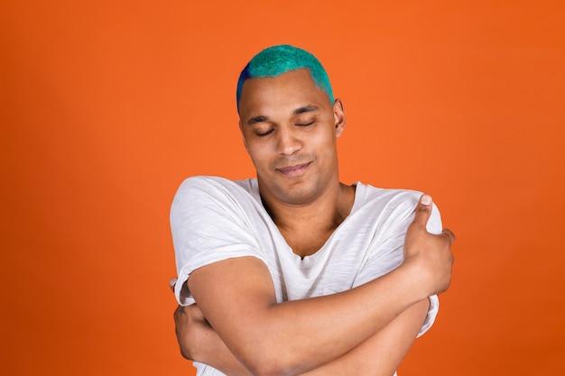Young man on orange wall hugging himself