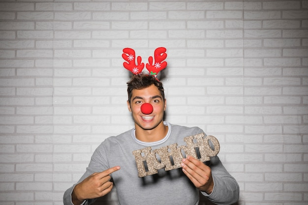 Young man in ornament deer antlers headband with sign