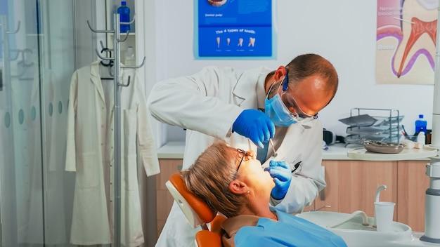 口腔病学クリニックで滅菌歯科用ツールを使用して高齢患者を検査する若い男性の歯科矯正医。看護師がランプを点灯し、医師が口腔病学の椅子に座っている患者に話しかけます。