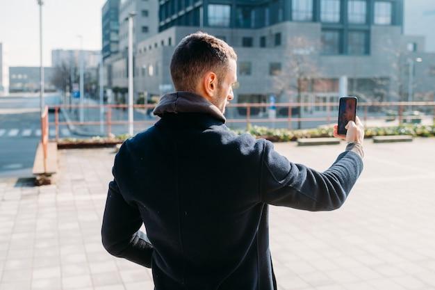 Young man outdoor using smart phone taking selfie