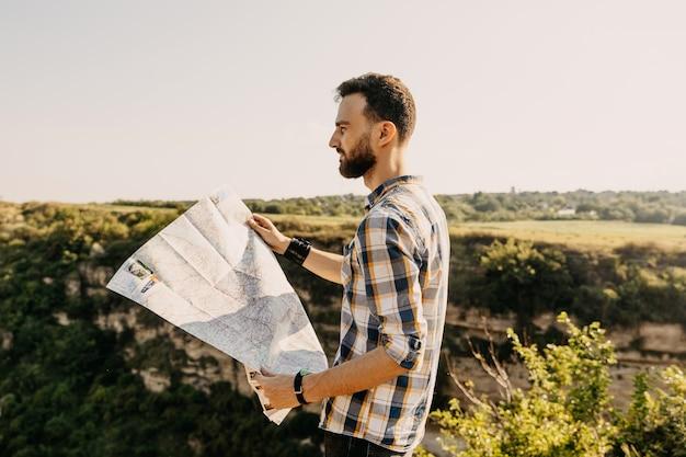 Молодой человек на открытом воздухе держит бумажную карту.