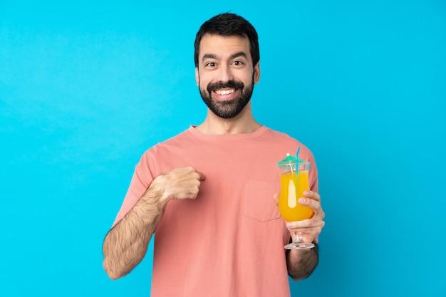 Молодой человек за коктейль над синей стеной с удивленным выражением лица
