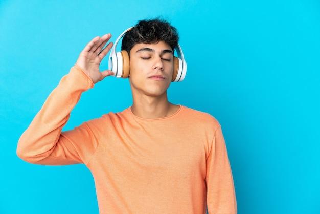 Молодой человек на изолированном синем фоне слушает музыку и танцует