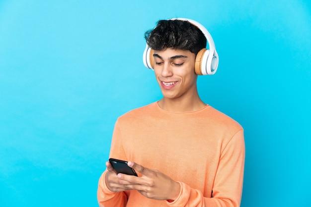 Молодой человек над изолированной синей стеной слушает музыку и смотрит на мобильный