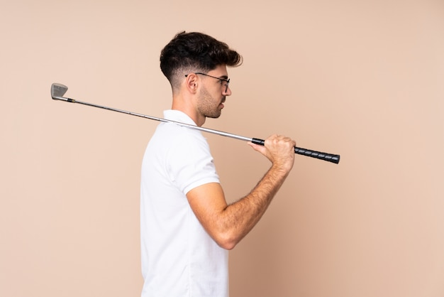 Молодой человек над изолированной игрой в гольф