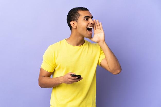 Молодой человек над изолированной фиолетовой стеной, используя мобильный телефон, кричит с широко открытым ртом