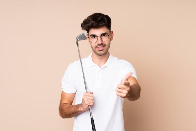Молодой человек за изолированной стеной, играя в гольф и указывая на фронт