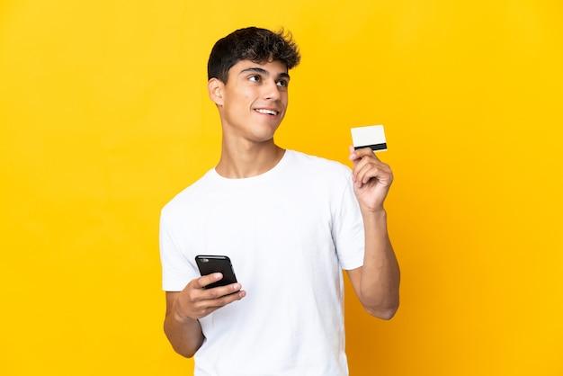 Молодой человек над изолированной желтой покупкой с помощью мобильного телефона с помощью кредитной карты, думая