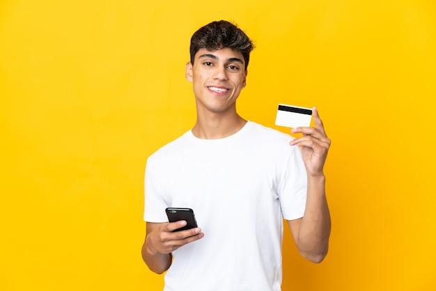 Молодой человек над желтым покупает мобильный телефон с помощью кредитной карты