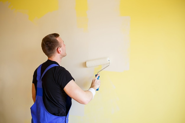 Young man in overalls hold a paint roller. tools accessories for apartment room renovation. home renovation concept