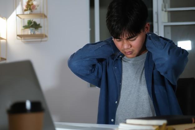 젊은 남자는 초과 근무를하고 집에서 어깨와 목의 통증을 느낍니다.