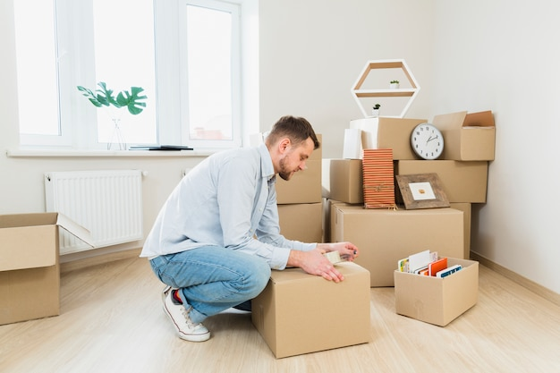 Young man packing the cardboard boxes at home