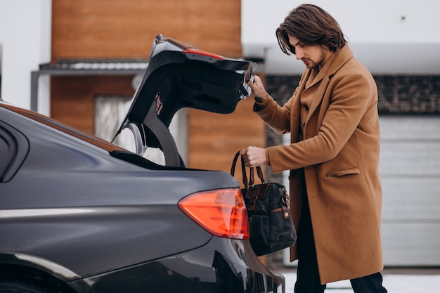 Young man packing his bag into a car