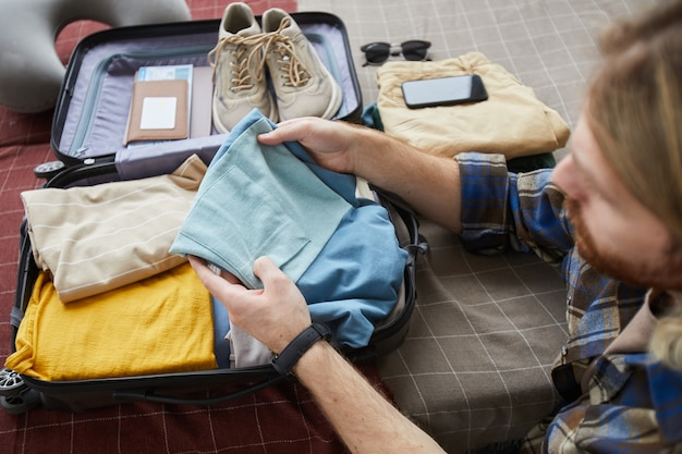 Young man packing his clothes in suitcase for summer vacations