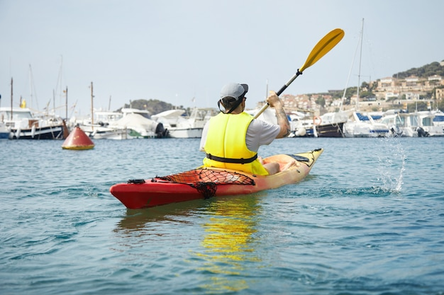 Young man paddling on red kayak on the sea near ships and yachts. tourist making splashes with paddle of canoe.