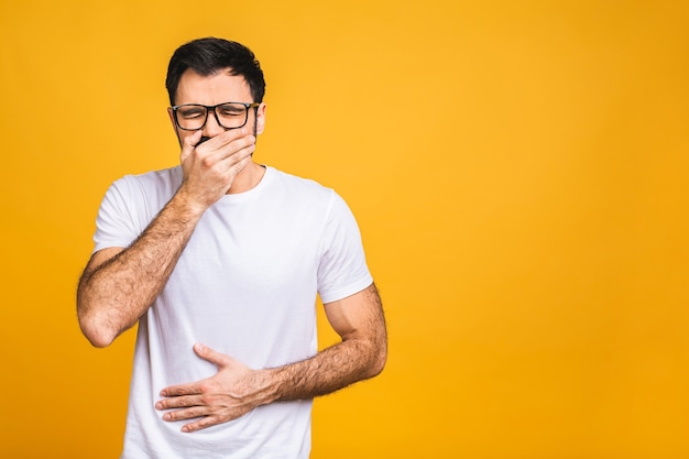Young man in pain holding his hurting stomach isolated on the yellow background. abdominal pain.