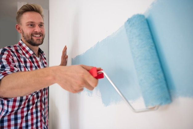 Молодой человек рисует синюю стену