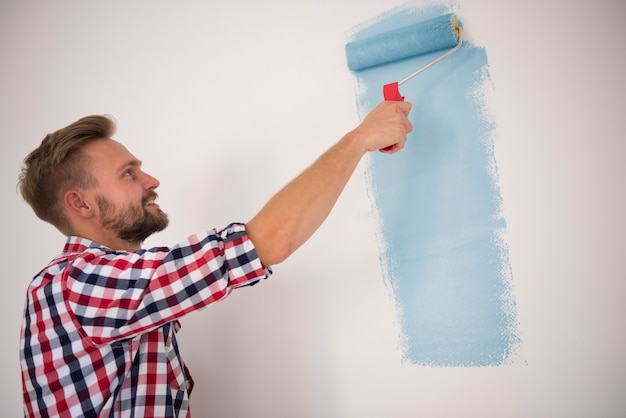 Young man painting a blue wall