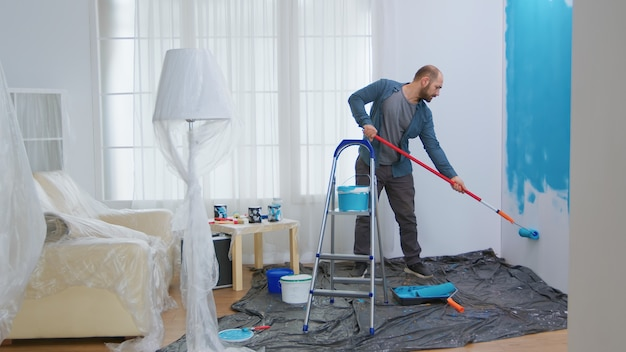Young man painting wall with roller brush while renovating his apartment. handyman redecoration and home construction while renovating and improving. repair and decorating.