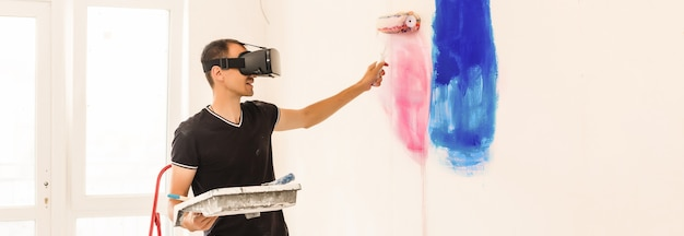 Young man painting the wall with virtual reality goggles