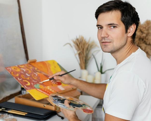 アクリル絵の具で絵を描く若い男
