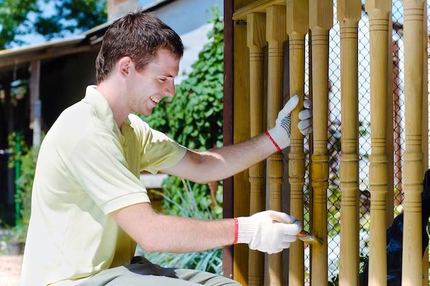 若い男が庭で木製のフェンスを塗る