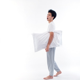 Young man in pajamas embracing white pillow isolated