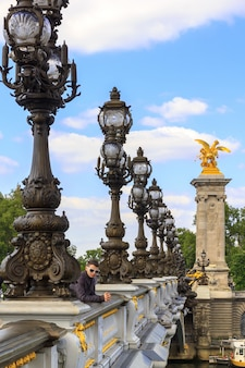 A young man in paris on the bridge of alexander iii, france