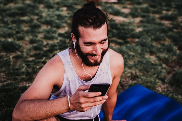 Young man in a park listening to music on mobile phone