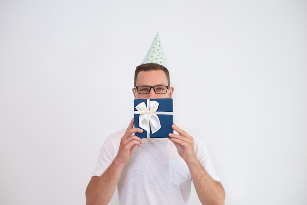 Young man in party hat covering mouth with gift box