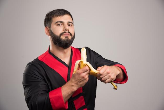 Молодой человек чистит банан на темной стене.