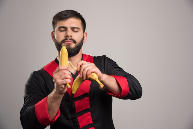 Young man peeling a banana on dark wall.