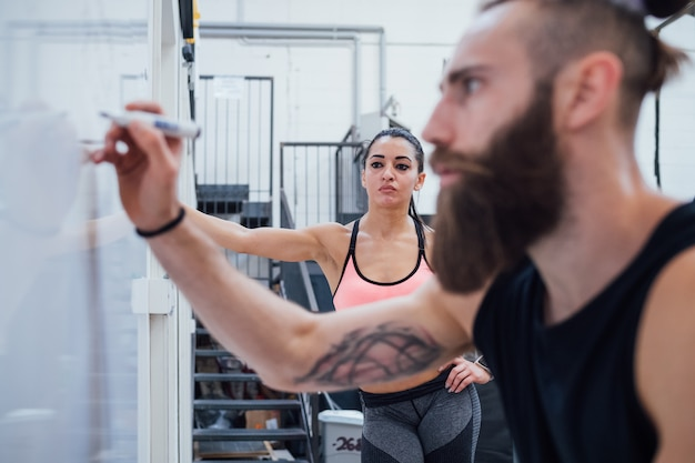 Young man personal trainer indoor gym writing on whiteboard planning training for athlete woman