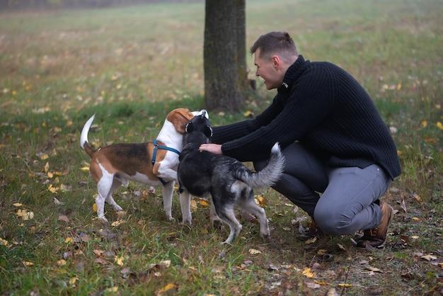 Владелец домашнего животного молодой человек с собакой в осеннем парке