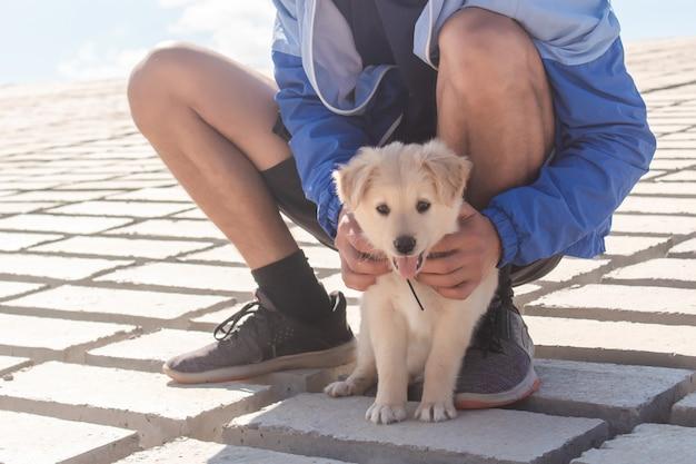 外で彼の子犬をかわいがる若い男。