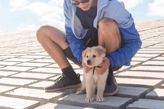 ジョギングに出かけている間、彼の子犬をかわいがる若い男。