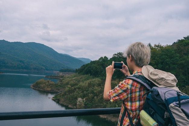 Young man photo trekker use smartphone take photo enjoy traveling with backpack